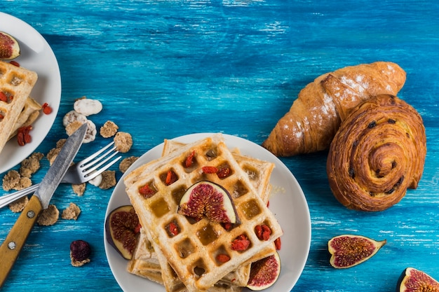 French pastries; corn flakes and waffles on fig over the wooden background