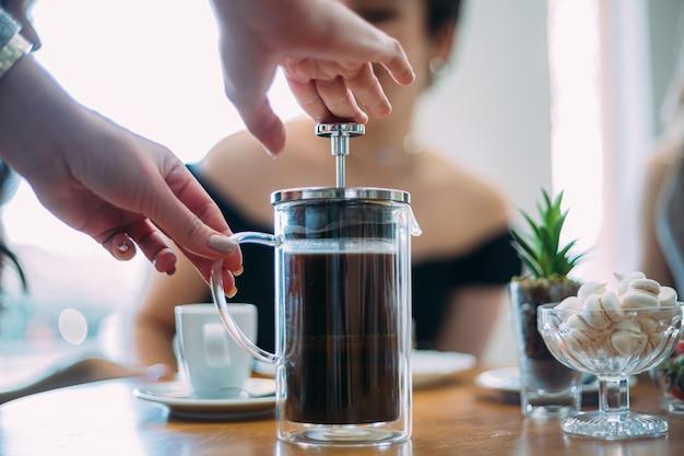 フレンチプレスコーヒー。ブラジルのカフェショップのテーブルでコーヒーを待っている友達。