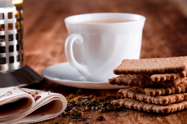 French press, cup of fresh herbal tea and some cookies closeup on wooden table