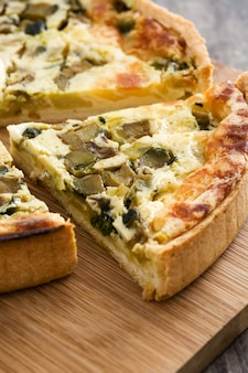 French quiche lorraine slice with vegetables on a rustic wooden table.