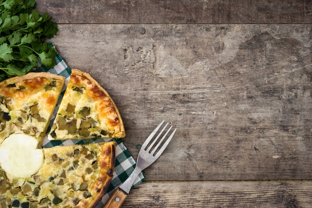 French quiche lorraine with vegetables on a rustic wooden table. top view.