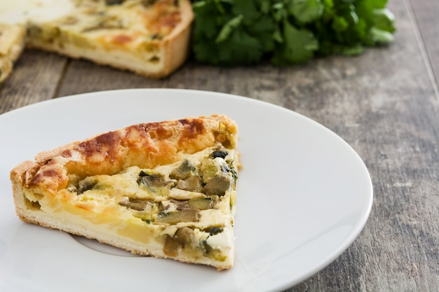French quiche slice with vegetables on a rustic wooden table