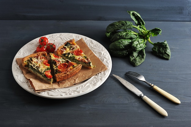 French quiche with eggs, fresh spinach, tomatoes and bacon