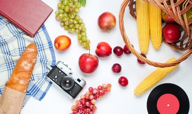 Французский пикник в стиле ретро. корзина с фруктами и овощами, ретро фотоаппарат, книга, багет и другие продукты для пикника на белом фоне.