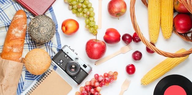 フランスのレトロなスタイルのピクニック。果物や野菜、レトロなカメラ、本、バゲット、その他のピクニックフードの白い背景のバスケット。