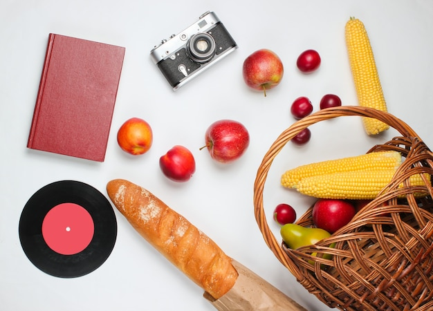 French retro style picnic. basket with fruits and vegetables, retro camera, book, baguette and other picnic food white background.