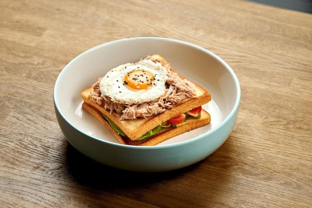 Французский сэндвич croque madame с яйцом, огурцом, помидорами, авокадо и тунцом в тарелке на деревянном фоне
