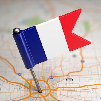 選択的な焦点と地図の背景上のフランスの小さな旗。