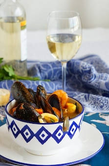 French soup bouillabaisse with mussels, clams, langoustines, squid, cod, trout in white bowl with blue patterns