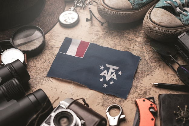 French southern flag between traveler's accessories on old vintage map. tourist destination concept.