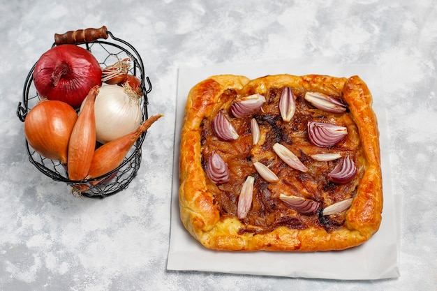 French style onion pie galette with puff pastry  and various onions shallot,red,white,yellow onions,top view