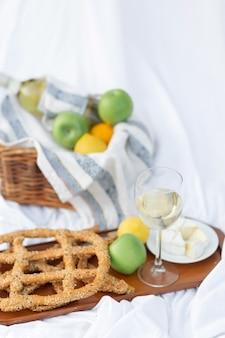 프랑스 스타일의 낭만적인 피크닉 환경. 치즈, 와인, 사과, 마른 빵 세트. 여름 피크닉 공간을 위해 준비된 음식이 있는 담요, 흰색 시트