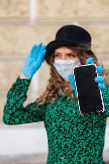Французская стильная молодая женщина в шляпе на улице с телефоном