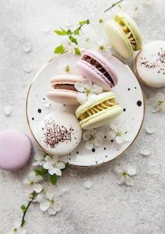Французские сладкие миндальное печенье красочное разнообразие на бетонной поверхности с весенним цветением