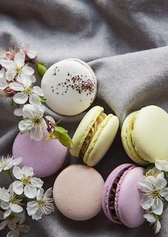 春の花と灰色のテキスタイルの背景にフランスの甘いマカロンカラフルな品種