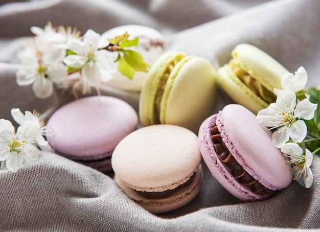 Французские сладкие миндальное печенье красочное разнообразие на сером текстильном фоне с весенним цветением