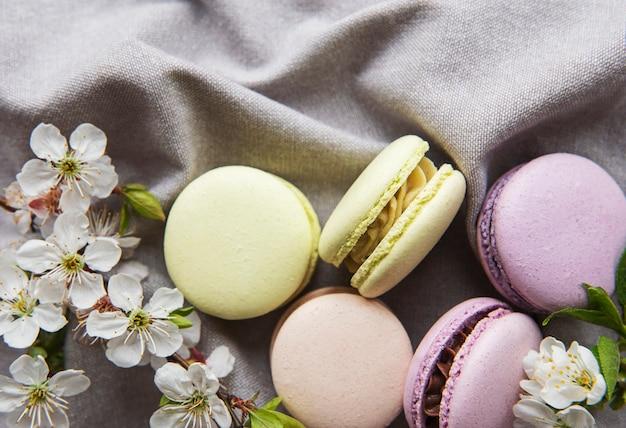 春の花を持つグレーの布地にフランスの甘いマカロンのカラフルな品種