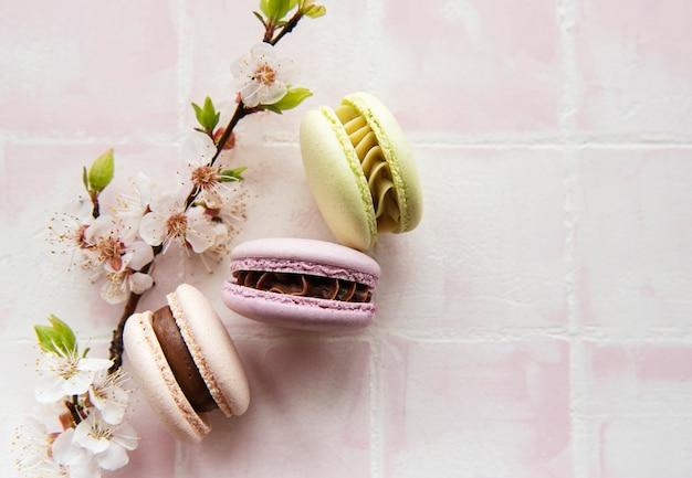 春の花とピンクのタイルの背景にフランスの甘いマカロンカラフルな品種