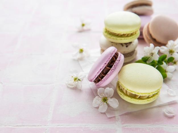 春の花とピンクのタイルの表面にフランスの甘いマカロンのカラフルな品種