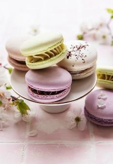 Французские сладкие миндальное печенье красочное разнообразие на поверхности розовой плитки с весенним цветением