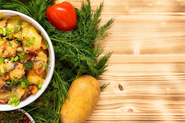 Reblochon 치즈와 베이컨 샐러드와 함께 나무 테이블에 프랑스 tartiflette. 공간을 복사하십시오. 평면도.