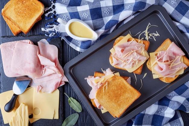 Французские тосты croque monsieur, приготовленные для выпечки. поджаренный масляный хлеб с ломтиками вареной ветчины и сыром эмменталь на противне с ингредиентами на деревянном столе, вид сверху, плоская планировка