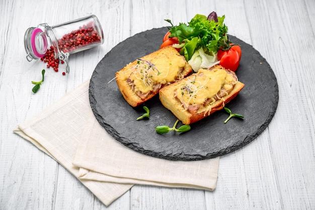フレンチトーストハムチーズとサラダを皿に盛り付けます。木製のテーブルの上