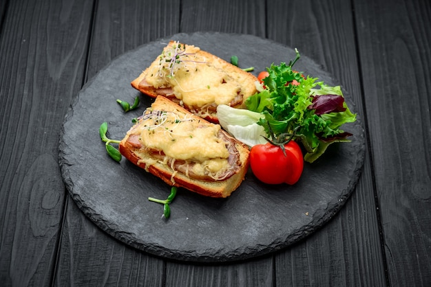 French toast ham cheese and salad on dish. on the wooden table