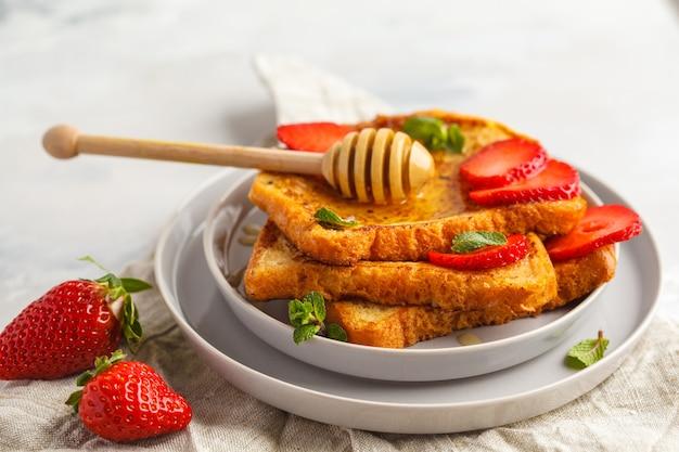 Французский тост с медом и клубникой в серой тарелке. серый фон