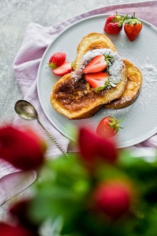 French toast with strawberries. vase with roses.