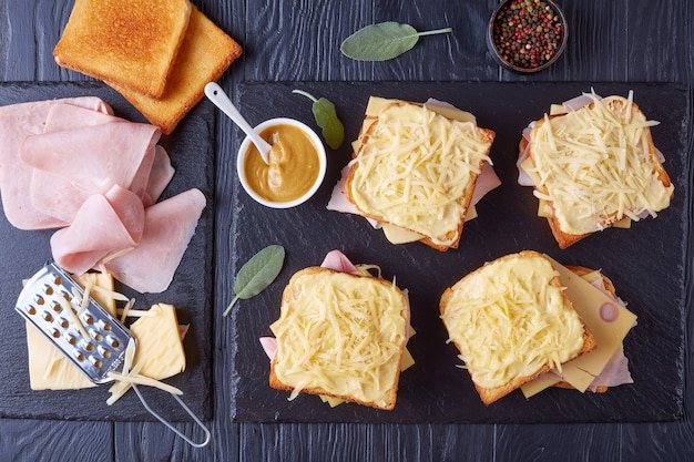French toasts croque monsieur prepared to bake. toasted butter bread with slices of boiled ham and emmental cheese on a baking sheet and ingredients on a wooden table, view from above