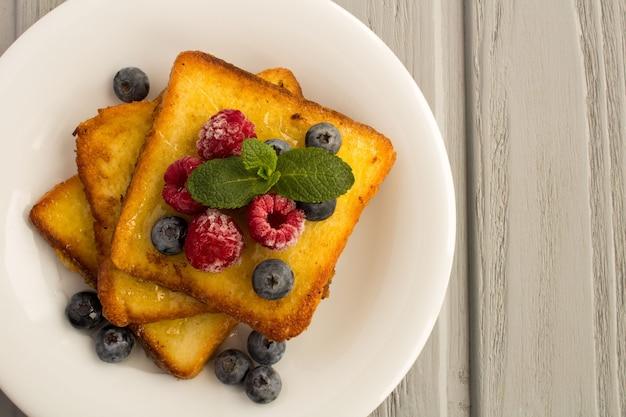灰色の木製の背景の白いプレートにベリーと蜂蜜とフレンチトースト。上面図。コピースペース。