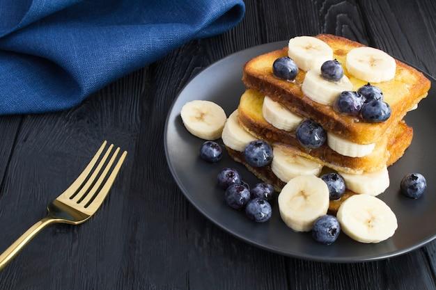 ブルーベリー、バナナ、暗い背景の木の黒い皿に蜂蜜とフレンチトースト。閉じる。