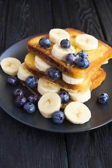 ダークウッドの背景に黒いプレートでブルーベリー、バナナ、蜂蜜とフレンチトースト。場所は垂直です。閉じる。