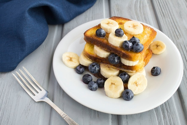 French toasts with blueberries and  banana in the white plate on the  gray surface