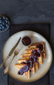 French toasts with blueberry jam on gray concrete. top view.