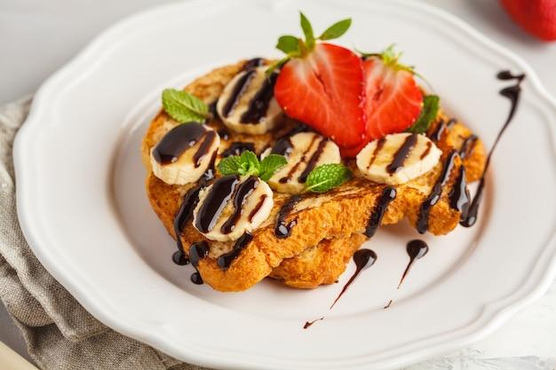 フレンチトーストとチョコレートシロップ、イチゴ、バナナ。灰色の背景、コピースペース、トップビュー。
