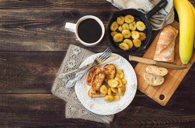 French toasts with fried bananas for breakfast on rustic wooden table. top view.