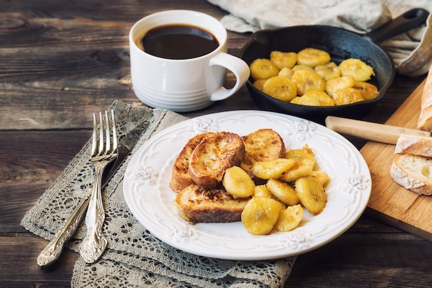 French toasts with fried bananas for breakfast on rustic wooden table Premium Photo