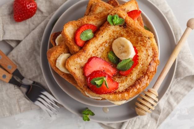 Французские тосты с медом, бананом и клубникой на серой тарелке. серый фон, копия пространства, вид сверху.
