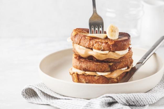 땅콩 버터와 하얀 접시에 바나나 프렌치 토스트.