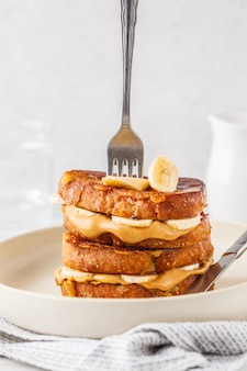 French toasts with peanut butter and banana on a white plate.