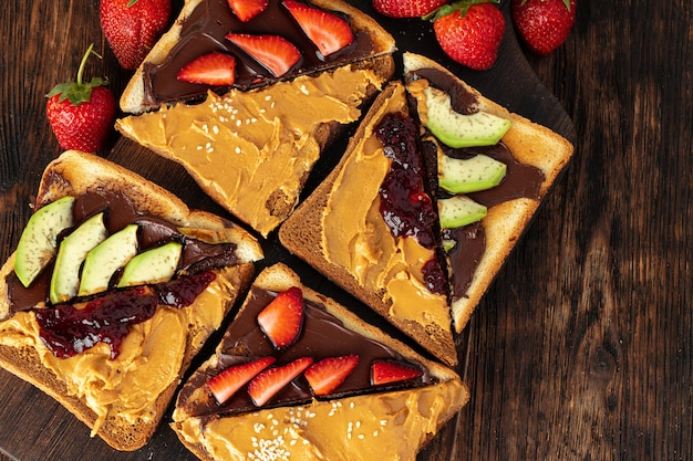 French toasts with peanut butter and fruit pieces on dark wooden table