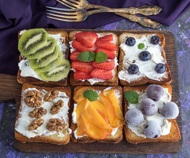 French toasts with soft cheese, strawberries, kiwi, walnuts, cherries and blueberries