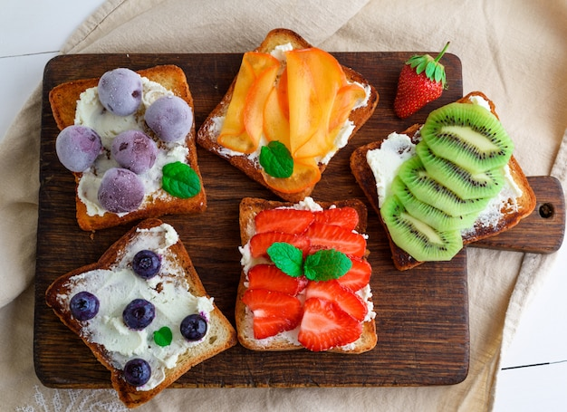 French toasts with soft cheese, strawberries, kiwi, walnuts