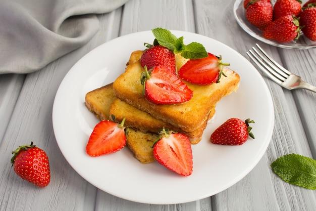 灰色の木製の白いプレートにイチゴと蜂蜜のフレンチトースト