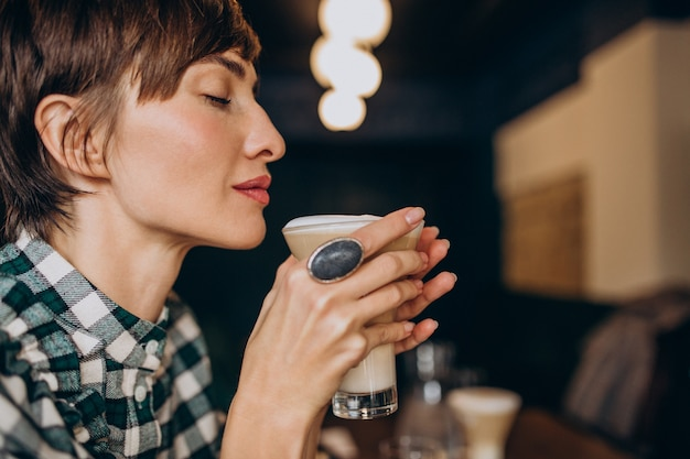French woman in cafe drinking latte