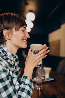 Donna francese in caffè che beve latte