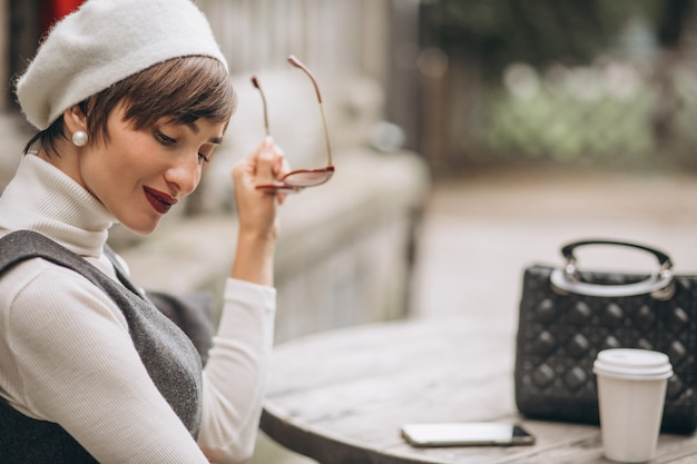 Donna francese che beve caffè nella caffetteria sulla terrazza