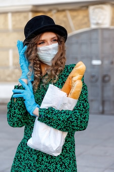 French woman in hat, medical mask and rubber gloves on street with baguettes smiles through protective mask. concept of coronavirus pandemic. place for an inscription or logo